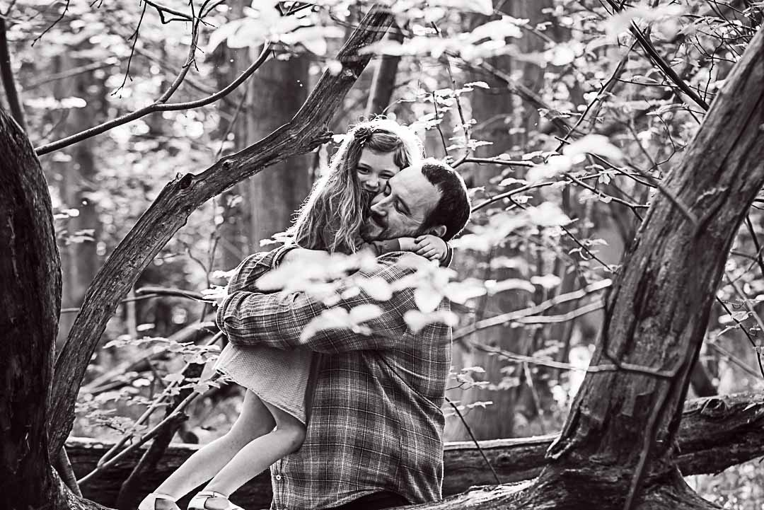 father and daughter cuddle in the woods