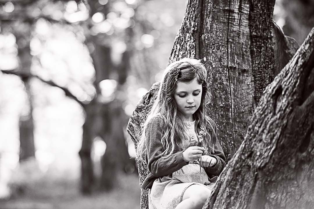 Little girl in the woods with a flower
