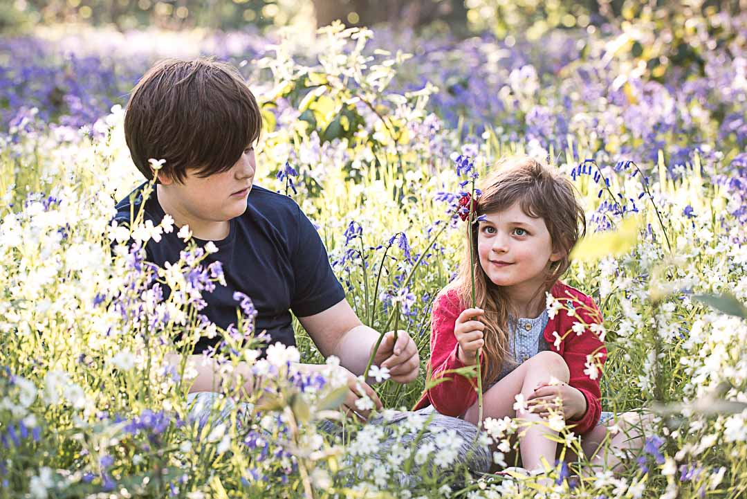Brother and sister in the bluebells at golden hour