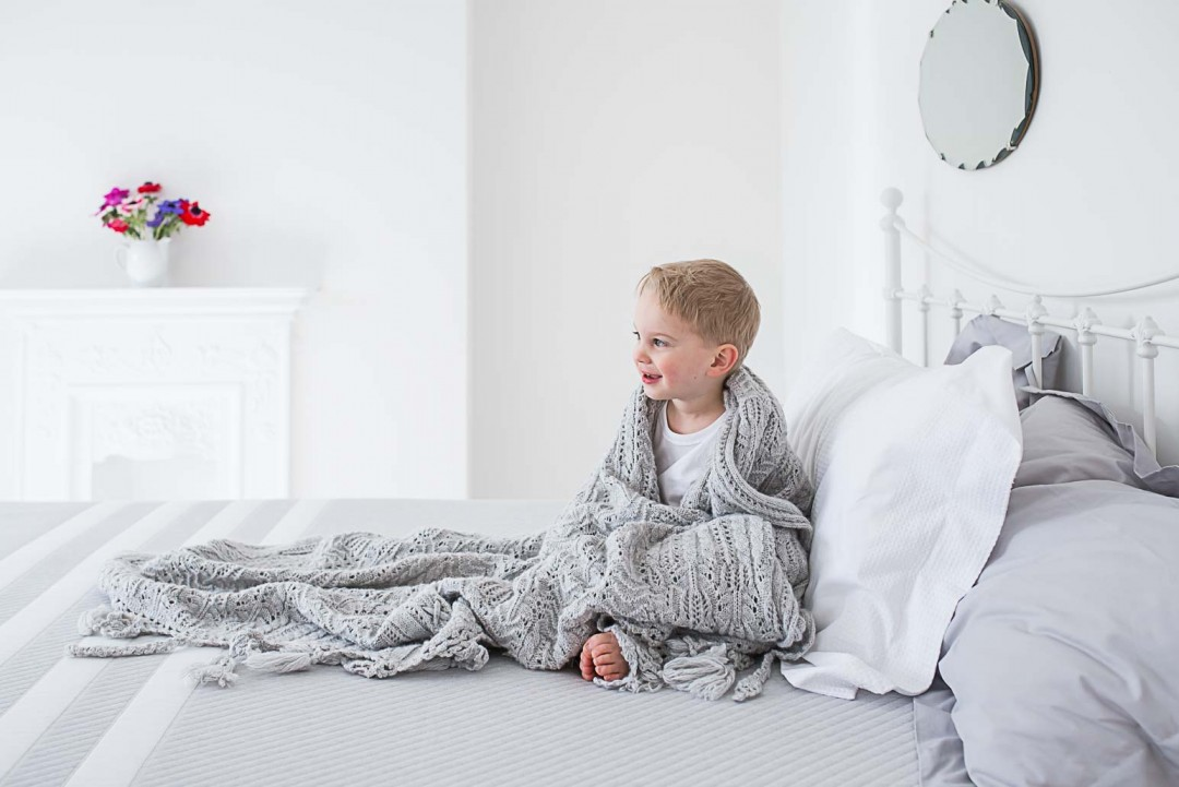 Happy little boy wrapped in a blanket in his parent's bed room, with Leesa UK mattress